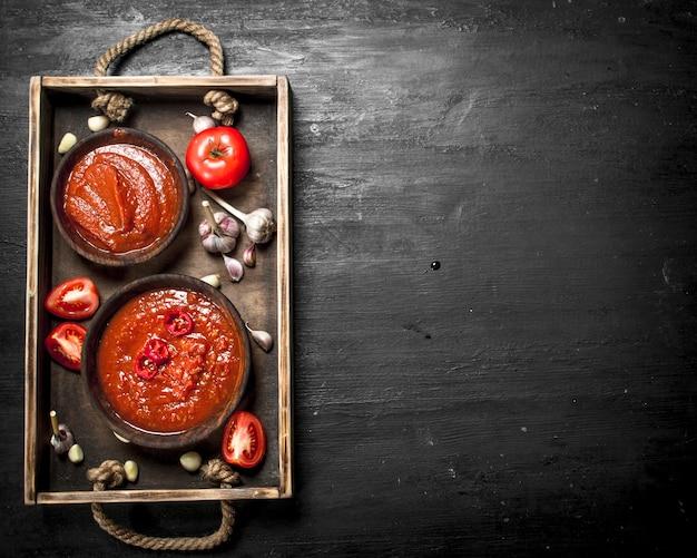 Sauce tomate fraîche aux épices et ail sur plateau en bois. sur tableau noir.