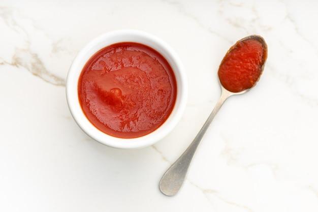 Sauce tomate fraîche sur bol et cuillère sur table en marbre blanc