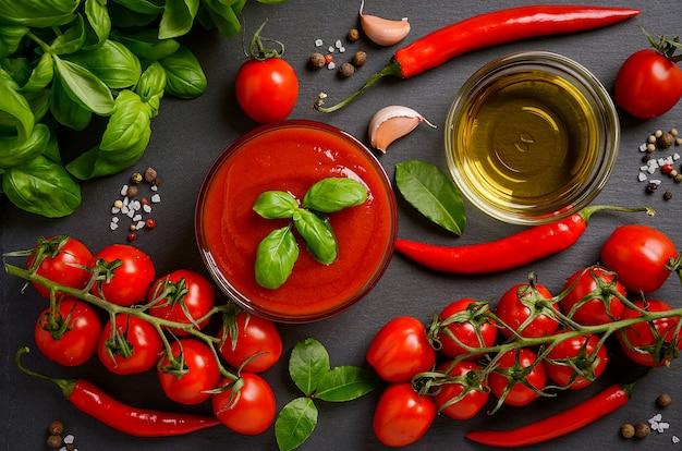 Sauce tomate avec des ingrédients sur fond noir.