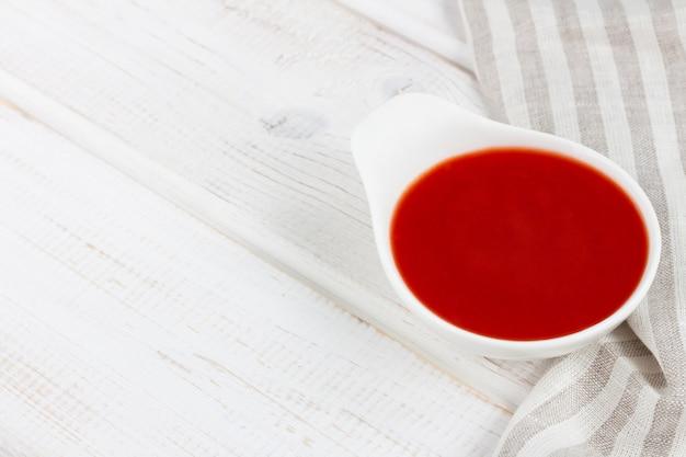 Sauce tomate (ketchup) dans une saucière sur une table en bois blanc