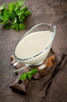 Sauce vanille avec des branches de menthe fraîche sur fond sombre