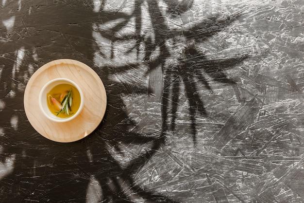 Sauceboat avec de l'huile sur un socle en bois sur une table