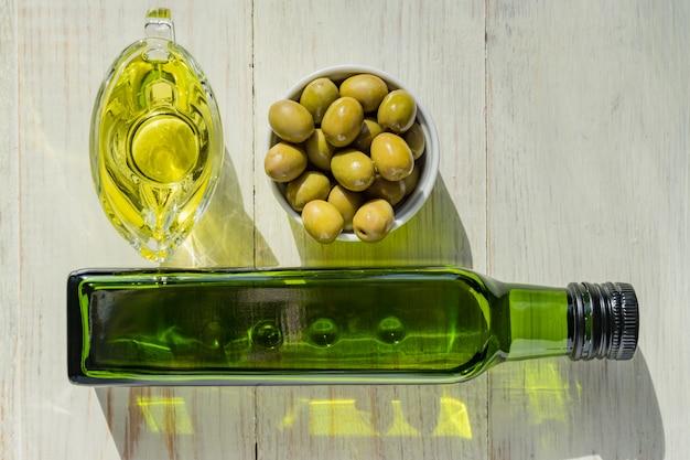 Saucière en verre avec de l'huile d'olive extra vierge, des olives vertes fraîches et une bouteille sur une table en bois.