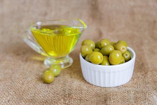 Saucière en verre avec de l'huile d'olive extra vierge et des olives vertes fraîches dans un bol en céramique blanche