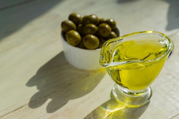 Saucière en verre avec de l'huile d'olive extra vierge et des olives vertes fraîches sur une table en bois.