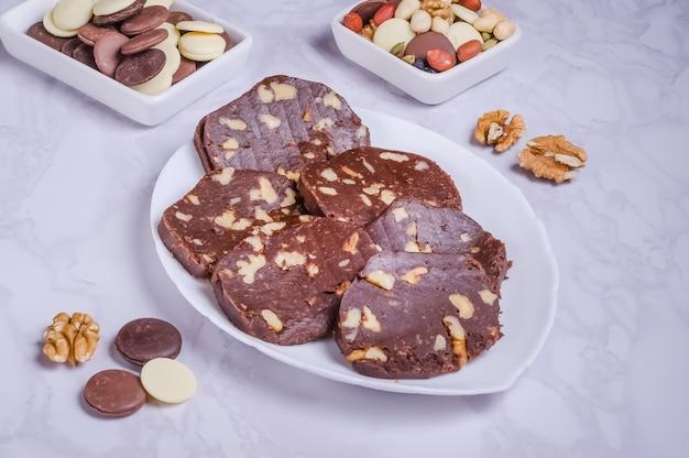 Saucisse au chocolat dessert aux noix sur une plaque blanche