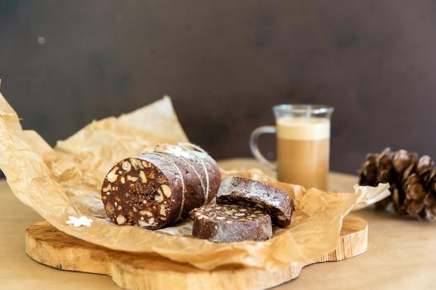 Saucisse au chocolat maison sur un fond en bois. dessert fait de biscuits, de chocolat et de noix est tranché sur une planche de bois