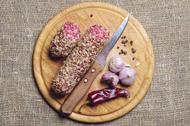 Saucisse aux graines de tournesol, piment rouge et ail sur planche à découper