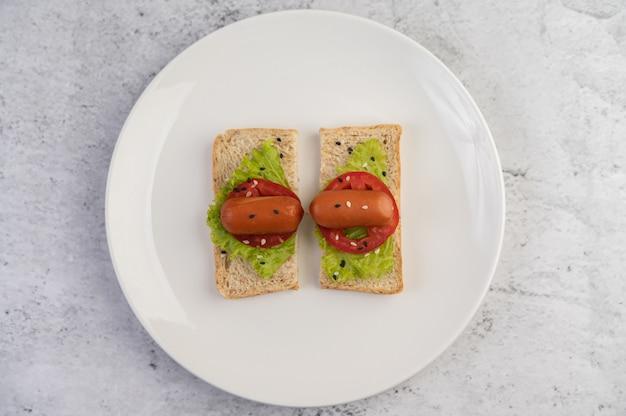 Saucisse aux tomates, salade et deux ensembles de pain sur une plaque blanche.