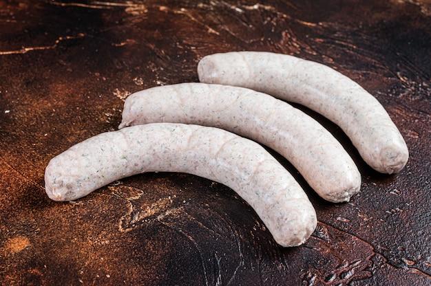 Saucisse blanche allemande crue weisswurst sur table de cuisine. fond sombre. vue de dessus.