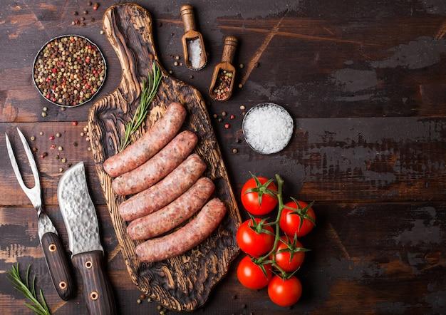Saucisse de boeuf et de porc crus sur une vieille planche à découper avec un couteau et une fourchette vintage