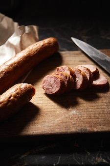 Saucisse de boeuf ou de porc fumé sur une vieille planche à découper avec couteau