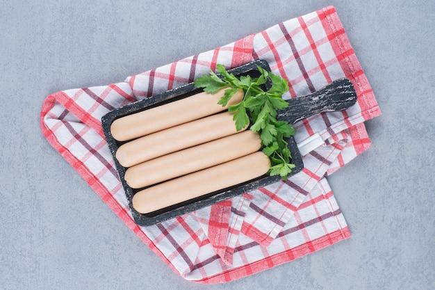 Saucisse bouillie fraîche sur une planche à découper en bois noir.