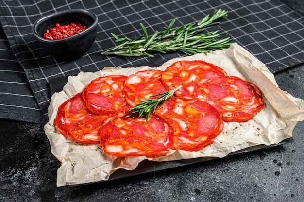 Saucisse chorizo au salami traditionnel. fond noir. vue de dessus
