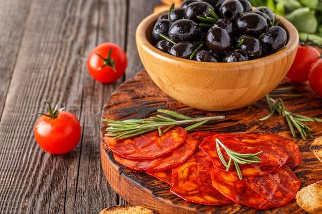 Saucisse chorizo traditionnelle espagnole aux herbes fraîches, olives, tomates sur une planche de bois