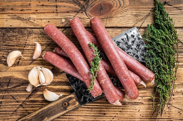 Saucisse crue de boeuf et de porc crue sur un couperet à viande vintage. fond en bois. vue de dessus.