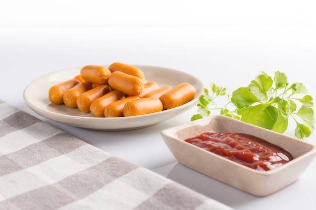 Saucisse dans un plat en céramique avec du ketchup préparez pour servir sur du blanc