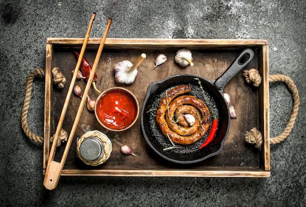 Saucisse dans une poêle avec de l'ail, du poivre et de la sauce tomate. sur un fond rustique.