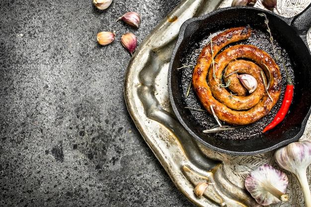 Saucisse dans une poêle avec des piments forts et de l'ail. sur un plateau en acier. sur un fond rustique.