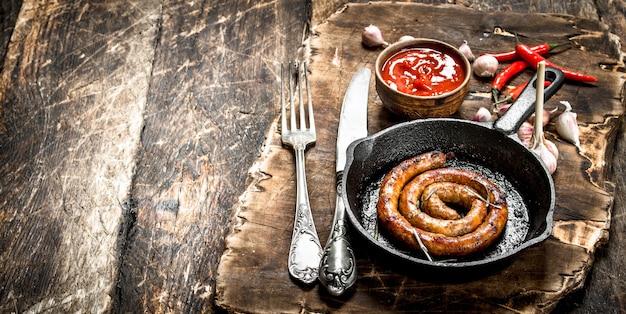 Saucisse dans une poêle avec sauce tomate et ail sur un fond en bois