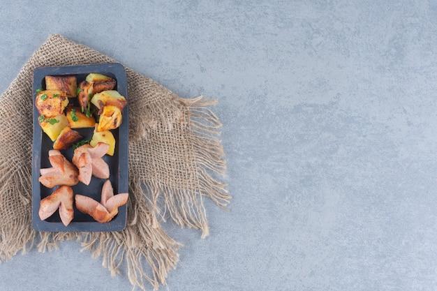 Saucisse frite aux pommes de terre sur une plaque en bois noire.