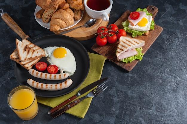 Saucisse frite avec des œufs et des légumes sur la casserole