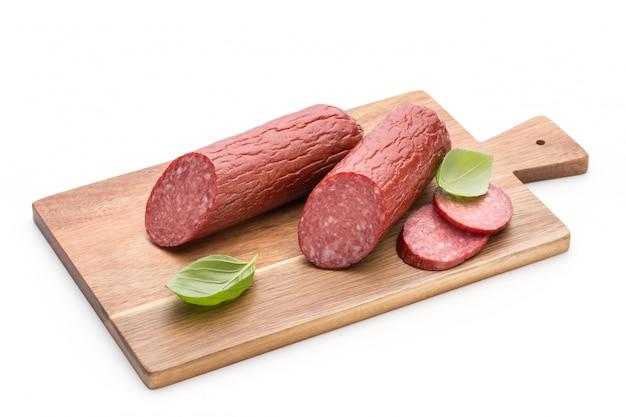 Saucisse fumée au salami, feuilles de basilic sur la découpe de l'espace blanc.