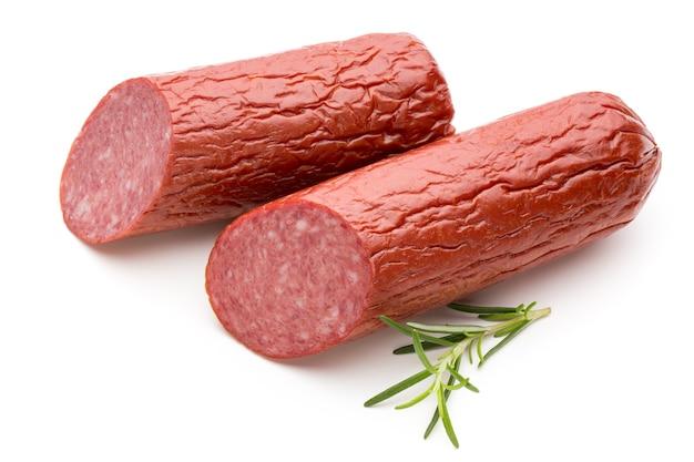 Saucisse fumée au salami, feuilles de basilic sur la découpe de surface blanche.