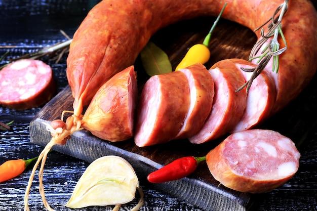 Saucisse fumée maison épices tranchées poivre ail romarin fond de bois foncé style rustique rétro vintage