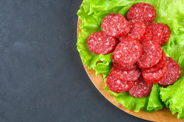 Saucisse fumée, salami haché en tranches sur une table en béton gris de planche à découper circulaire en bois de salade