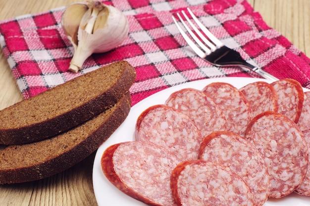 Saucisse fumée tranchée et pain sur table en bois