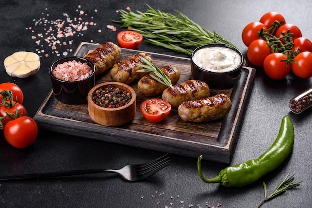 Saucisse grillée avec ajout d'herbes et de légumes sur fond sombre