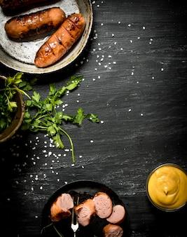 Saucisse grillée avec du persil et de la moutarde à la poêle. sur le tableau noir.
