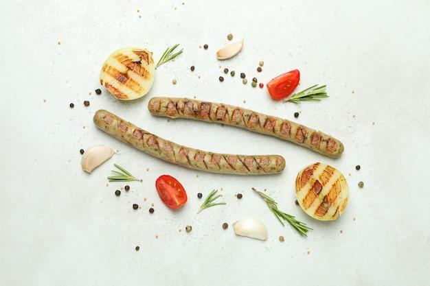 Saucisse grillée et épices sur une surface blanche