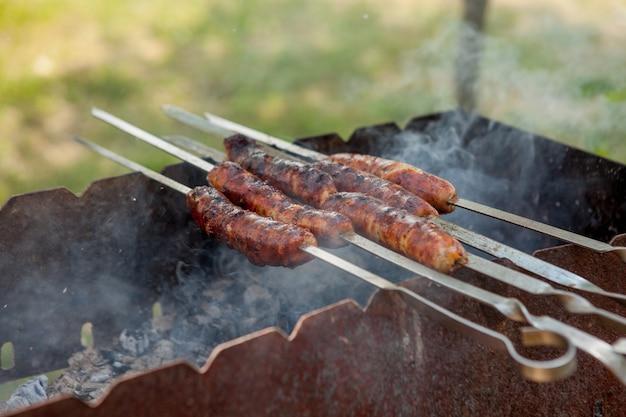Saucisse grillée sur le gril flamboyant de pique-nique.