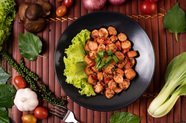 Saucisse larb aux oignons de printemps et laitue dans une assiette noire