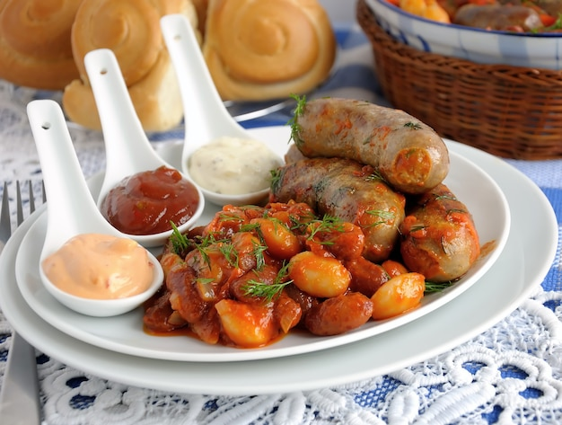 Saucisse maison aux haricots, oignons et carottes dans une sauce tomate