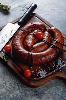 Saucisse maison cuite sur un gril, avec des tomates