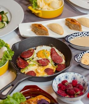 Saucisse et œuf pour le petit déjeuner avec des bonbons, des fruits, des baies