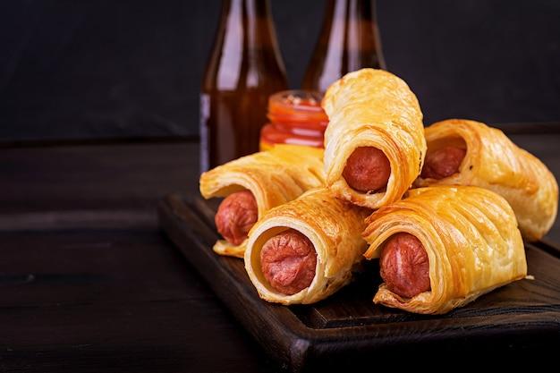 Saucisse à la pâte sur une planche de bois avec sauce tomate.