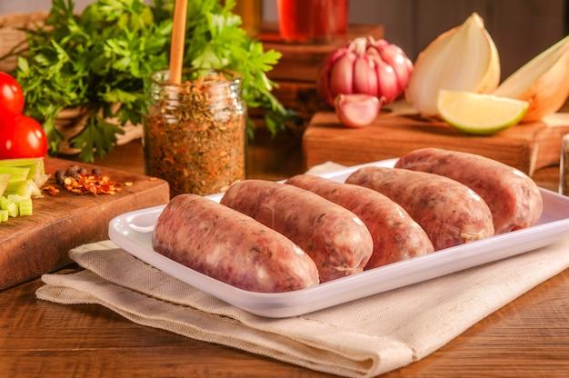 Saucisse de porc brésilienne avec chimichurri sur plaque blanche avec épices et ingrédients