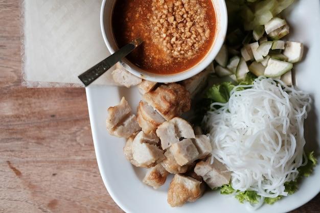 Saucisse de porc hachée, nouilles de riz fermentées et légumes servis avec une sauce chili.