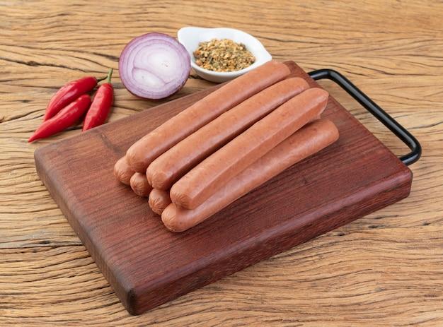 Saucisse de porc mince sur planche de bois avec assaisonnements.