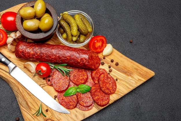 Saucisse salami bio séchée ou chorizo sur planche à découper en bois