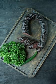 Une saucisse de sang sur une planche à découper sombre décorée de persil frisé.