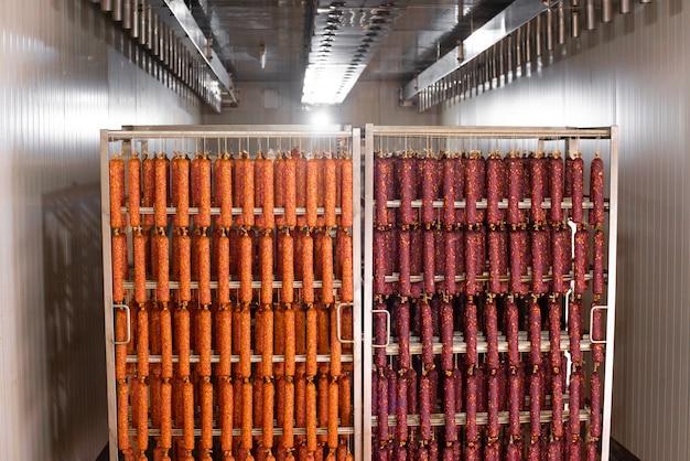 Saucisse séchée suspendue à une corde sur un cadre métallique dans le fumoir.