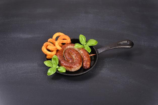 Saucisse en spirale épicée rôtie avec des feuilles de basilic et des frites frites dans une poêle