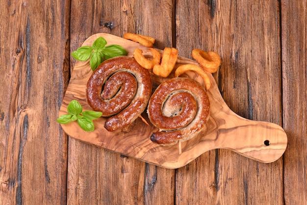 Saucisse en spirale épicée rôtie avec des feuilles de basilic et des frites frites
