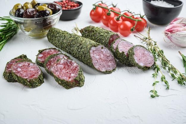 Saucisse traditionnelle de fuet aux herbes avec des ingrédients sur une table texturée blanche.