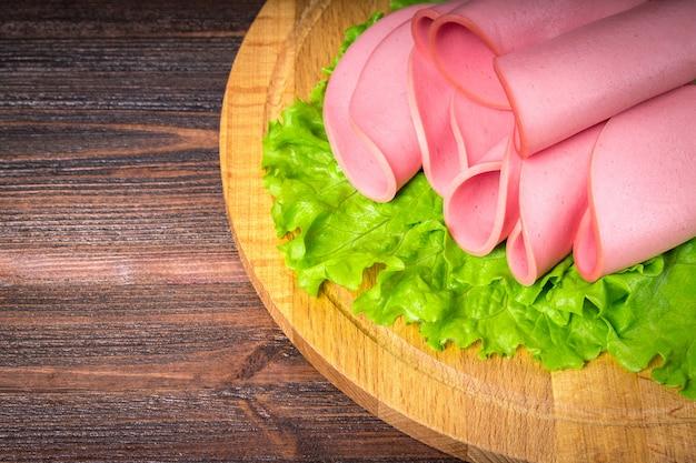 Saucisse en tranches avec de la salade sur une planche de bois ronde.